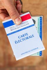 carte électorale française et carte d'identité tenues en main pour voter