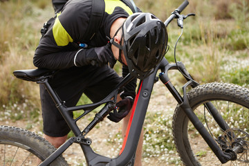 Cropped shot of male biker in helmet and gloves checking systems on black e-bike, leaning forward over his two-wheeled motor-powered vehicle. Young cyclist repairing or fixing pedelec in forest