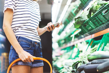 Young woman shopping healthy food in supermarket blur background. Female hands buy products and using mobile smart phone in store. Hipster at grocery holding basket. Person comparing price of produce