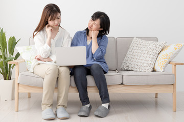 ノートパソコンを使う親子、母、娘、悩む