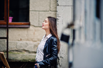 Portrait of stylish young girl wear on leather jacket and ripped jeans at streets of city. Street fashion model style.