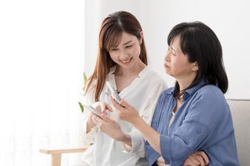 母に携帯電話の操作を教える娘、スマートフォン