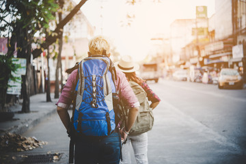 Young tourists couple with backpacks sightseeing cit. Couple traveling together in holiday.