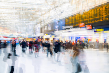 Multiple exposure image of lots of people walking and waiting for boarding in the Waterloo train station. Commuting rush hours concept, modern life.