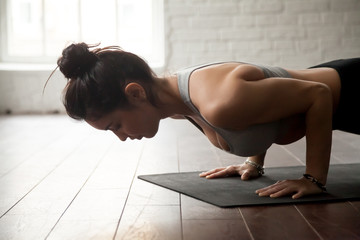 Young attractive woman practicing yoga, standing in chaturanga dandasana exercise, four limbed staff, Push ups or press ups pose, working out, white loft studio background, closeup