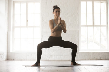 Portrait of young attractive yogi woman practicing yoga concept, standing in Sumo Squat exercise, Goddess pose, working out, wearing sportswear bra and pants, full length, white loft studio background
