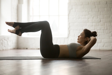 Young attractive cool woman practicing Abdominal Knee Crunches for upper and lower abs exercise, Sit Ups, working out, wearing black sportswear, full length silhouette on white loft studio background