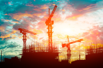 Crane and building construction site at sunset
