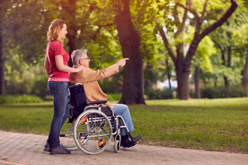 enjoying in family time elderly man in wheelchair and daughter in the park.