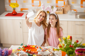 Woman with daughter make Easter selfie in kitchen