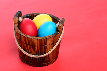 painted easter colorful eggs in wooden bucket on red background