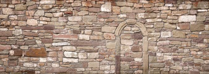 Panorama einer alten Mauer mit zugemauertem Torbogen