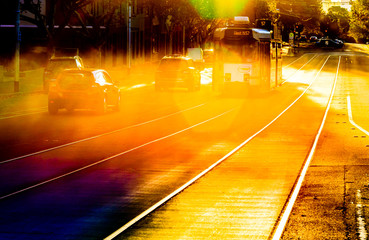 A famous Melbourne tram on its tracks on a bright summer afternoon with colorful lens flare.