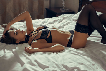 Sexy brown-haired woman in an erotic pose is lying on the bed and touches her hair with her hand. Close-up.