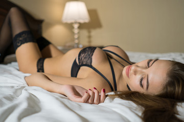Young Beautiful girl at bed. Cheerful, happy, sexy woman enjoying a relaxing stay in her bed.