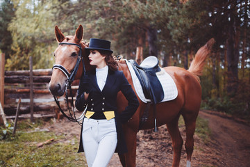Portrait, riding, concept of advertising equestrian club caring for a horse. Jockey girl next to the horse. Corrects the bridle. Summer. Toning.