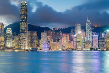 Night light Hong Kong city over Victoria bay with clear blue sky background, cityscape background