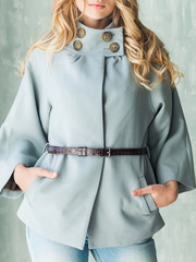 Young blonde woman in blue coat and blue jeans. Hands in pockets, brown leather belt