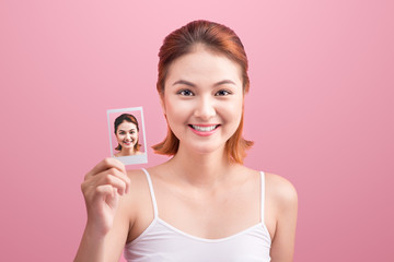 Young asian woman holding her polaroid picture on pink background.