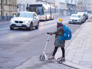 Autoverkehr - Kind wartet mit Scooter am Fahrbahnrand
