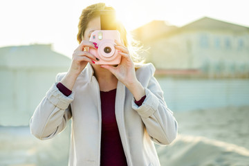 Young woman shooting with pink instant camera