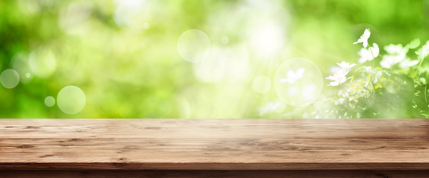Radiant green spring background with wooden table