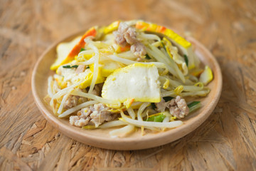 Stir-fried bean sprout with yellow tofu on wooden dish