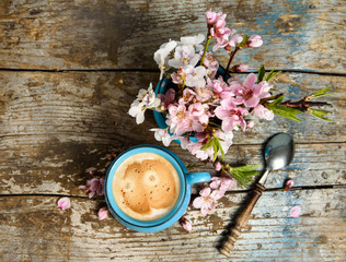 cup of Coffee with pink blooming flowers on grunge, old wood background top view. good morning post card, banner design