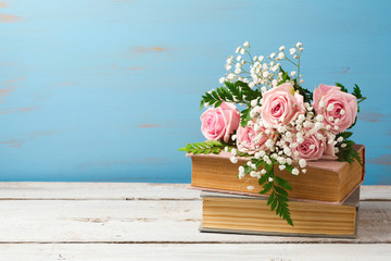 Rose flower bouquet on old books over wooden background with copy space