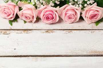 Background with rose flowers on wooden vintage table