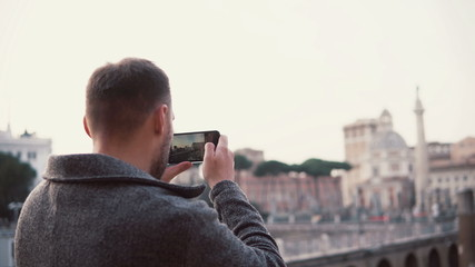 Handsome man with a beard exploring new city, taking photos of city on smartphone. Guy have vacation in Rome, Italy.