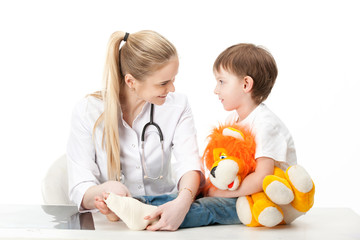 Doctor woman and child patient . Bandaging the leg with a bandage . Isolated white background .