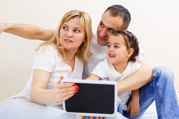 Young happy family running on a laptop. Family of three people looking at a computer screen. Mom, dad and daughter make purchase in the online store.