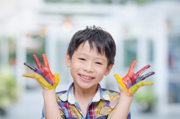 Little Asian boy with painted hands at home