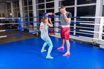 Athletic young couple in sportswear practicing boxing in regular boxing ring