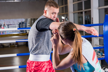 Portrait of young athletic male and female in sportswear boxing