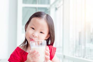 Little asian girl drinking a glass of milk