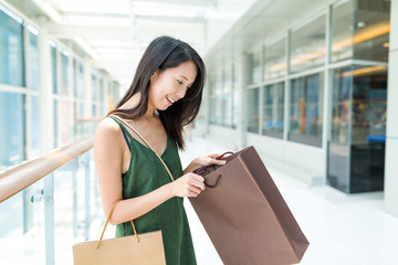 Woman checking the gift from shopping bag