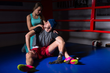 Young athletic woman support and hug her boyfriend in a boxing ring