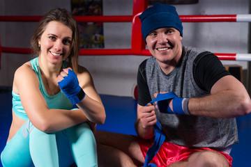 Smiling athletic boxing couple preparing bandages