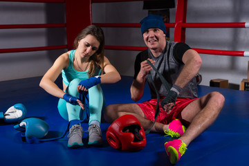 Boxing couple preparing bandages for fight near lying boxing gloves and helmet