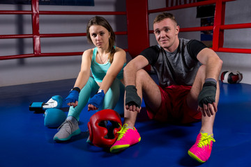 Boxing couple sitting near lying boxing gloves and helmet