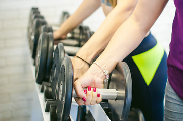 girl in a bright white gym. Two young athletic women near sports equipment are preparing for the traning with dumbbells, holding up in their hands. Healthy way of life, good spirits
