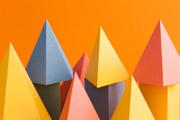 Abstract colorful geometrical background. Three-dimensional prism pyramid objects on orange paper. Yellow blue pink green colored solid figures, soft focus photo.