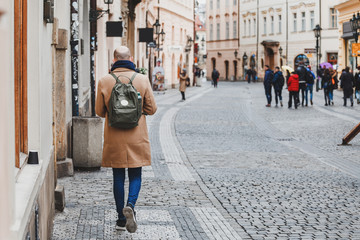 A walking bald hipster tourist with backpack in a European city street, view from the back