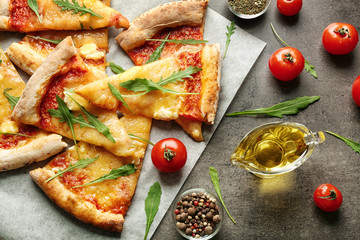 Tasty pizza slices with ingredients on table
