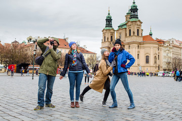 group of happy smiling multiracial friends walking and have fun in the old city of prague. Travel with friends concept