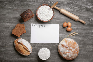 Blank paper sheet and ingredients for cooking bread on wooden background