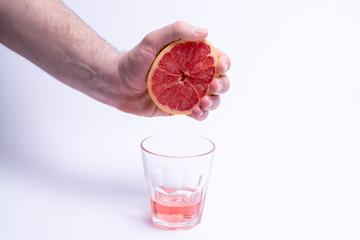 Male hand gripping grapefruit, grapefruit juice on white background