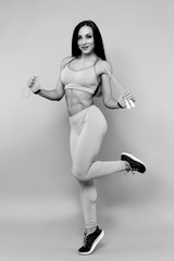 Sportive brunette girl in sportswear with skipping rope on the gray background in the studio.